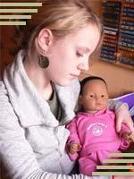 Junges Mädchen mit einem Babysimulator auf dem Arm (Foto: babybedenkzeit.de)